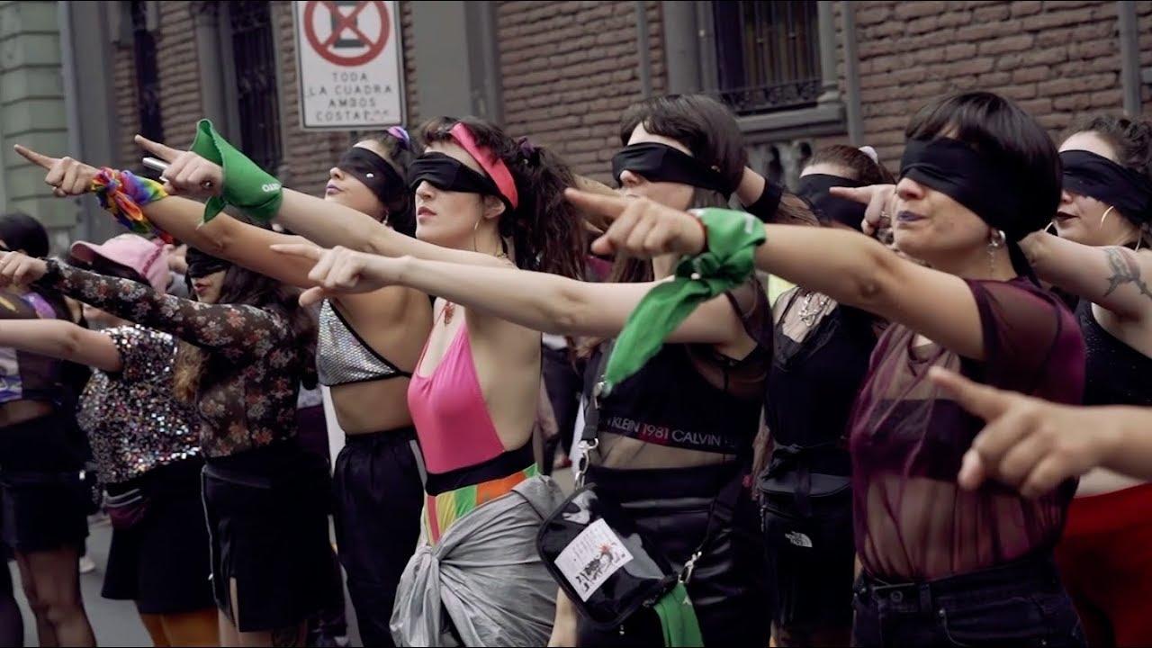 Para cego ver: mulheres chilenas com os olhos vendados, apontando para frente. Elas usam um lenço verde em seus punhos, símbolo da luta pelo aborto gratuito e legal.