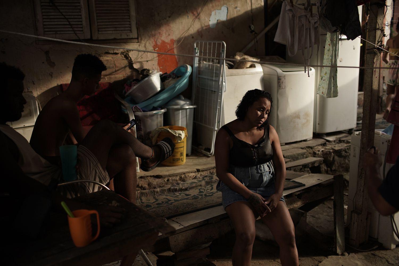 Mulher sentada ao lado dos filhos, no quintal de sua casa na favela do Turano, no Rio de Janeiro